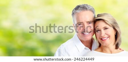 Happy senior loving couple over green nature background - stock photo