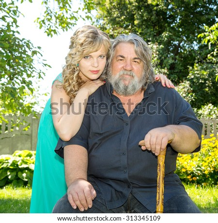 Happy senior man and his daughter in park. Portrait of smiling aged caucasian man with a gray beard on green park background. Smiling old man with a grey beard next to his daughter. Family father. - stock photo
