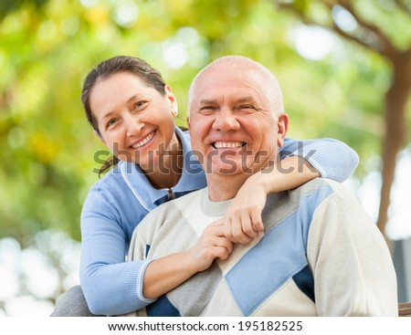 Happy senior man and mature woman against blured trees of forest - stock photo