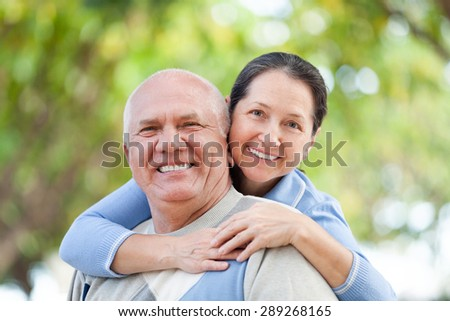 Happy senior man and smiling mature woman together against blured trees of park or forest