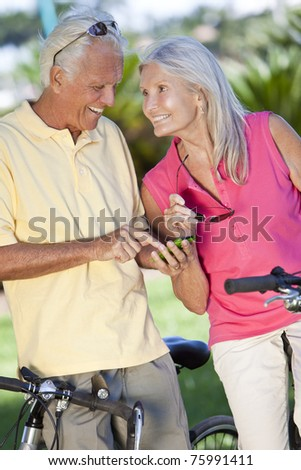 Happy senior man and woman couple cycling and together using a smart phone outside in sunshine - stock photo