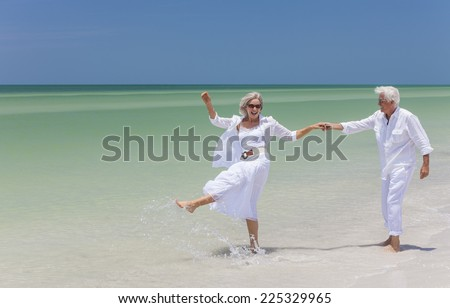 Happy senior man and woman couple dancing, holding hands & splashing in sea water on a deserted tropical beach with bright clear blue sky