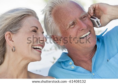 Happy senior man and woman couple laughing while talking on a mobile cell phone - stock photo