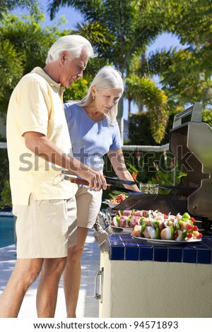Happy senior man and woman couple outside cooking kebabs on a summer barbecue