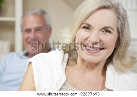 Happy senior man and woman couple sitting together at home smiling and happy - stock photo