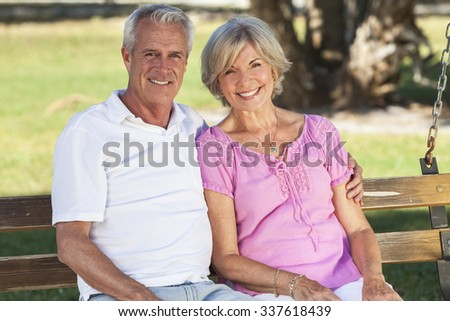 Happy senior man and woman couple sitting together on a park bench outside in sunshine - stock photo