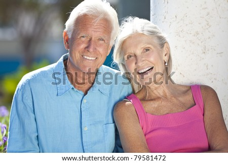 Happy senior man and woman couple sitting together outside in sunshine - stock photo