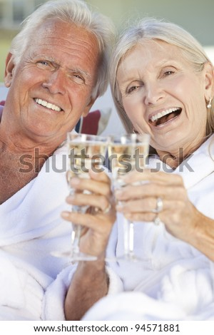 Happy senior man and woman couple sitting together outside in sunshine wearing white bathrobes celebrating drinking white wine Champagne - stock photo