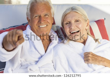 Happy senior man and woman couple sitting together wearing bathrobes at a health spa or on a cruise, the man is pointing - stock photo