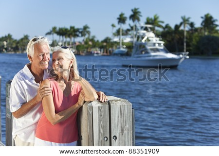 Happy senior man and woman couple together by a river or sea in a tropical location with a boat sailing past - stock photo