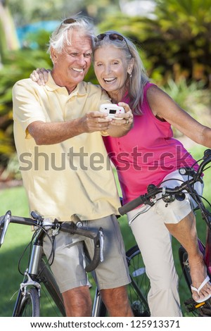 Happy senior man and woman couple together cycling on bicycles taking self portrait picture photograph with digital camera in a sunny green park - stock photo