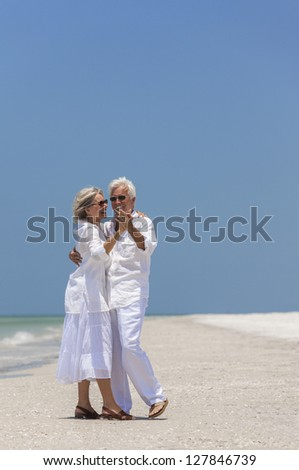 Happy senior man and woman couple together dancing by the sea on a deserted tropical beach with bright clear blue sky