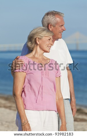 Happy senior man and woman couple together embracing and walking on a deserted tropical beach with a bridge in the background - stock photo