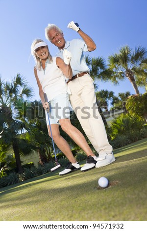Happy senior man and woman couple together playing golf and putting on a green, celebrating the ball going in the hole, a successful shot - stock photo