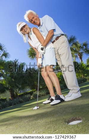 stock photo happy senior man and woman couple together playing golf and putting on a green the man is teaching 127429367