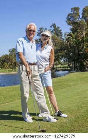 Happy senior man and woman couple together playing golf on a course near a lake - stock photo
