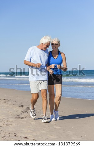 Happy senior man and woman couple together running or jogging by sea on a deserted tropical beach with bright clear blue sky - stock photo