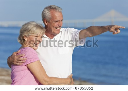 Happy senior man and woman couple together walking and pointing on a deserted beach - stock photo