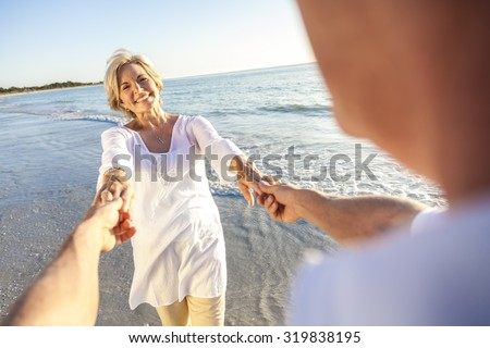 Happy senior man and woman couple walking or dancing and holding hands on a deserted tropical beach with bright clear blue sky - stock photo