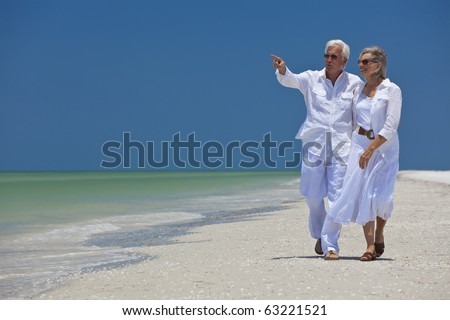 Happy senior man and woman couple walking together looking out to sea on a deserted tropical beach with bright clear blue sky, the man is pointing to the horizon - stock photo