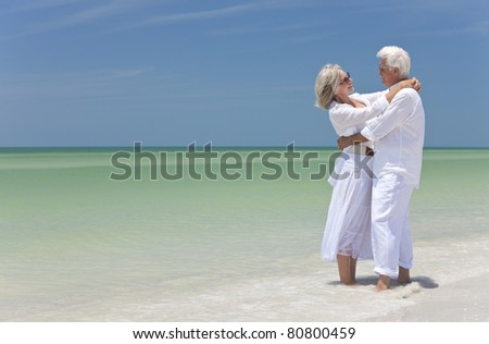 Happy senior man and woman embracing on a deserted tropical beach with bright clear blue sky - stock photo