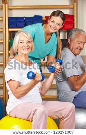 Happy senior man and woman in gym doing fitness in a nursing home - stock photo