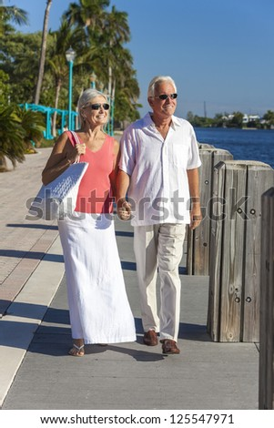 Happy senior man and woman romantic couple together looking out to tropical sea or river with bright clear blue sky - stock photo