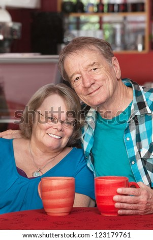 Happy senior man and woman sitting at table with mugs - stock photo