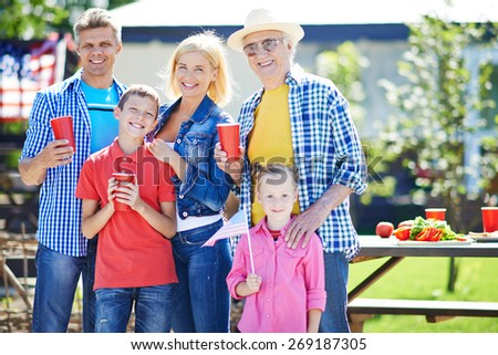 Happy senior man and young couple with two kids spending weekend outdoors - stock photo