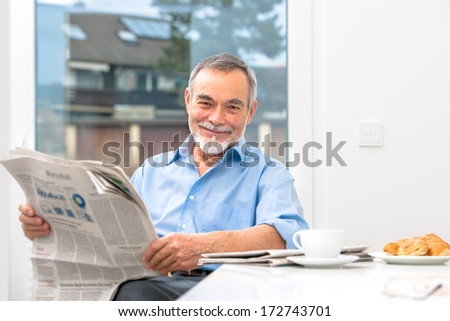 Happy senior man at breakfast with newspaper - stock photo