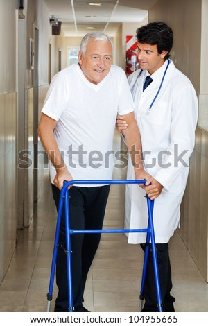 Happy senior man being helped by a male doctor to walk the Zimmer frame - stock photo