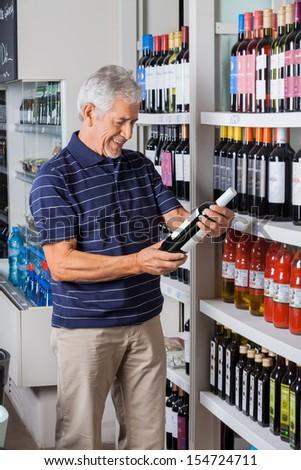 Happy senior man buying alcohol at supermarket - stock photo