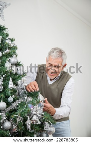 Happy senior man decorating Christmas tree with silver ornaments at home - stock photo