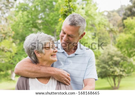 Happy senior man embracing woman from behind at the park - stock photo