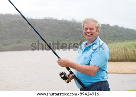 happy senior man fishing by the pond