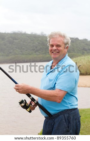 happy senior man fishing by the river - stock photo