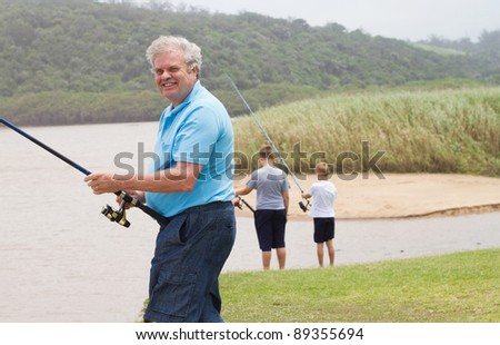 happy senior man fishing with grandsons by the lake - stock photo