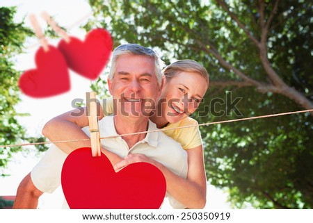 Happy senior man giving his partner a piggy back against hearts hanging on a line - stock photo