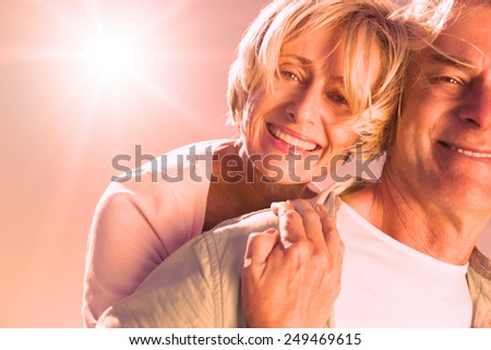Happy senior man giving his partner a piggy back on a sunny day - stock photo
