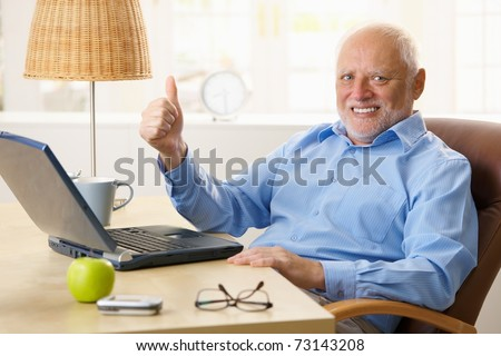 Happy senior man giving thumb up, sitting at desk using laptop computer at home.? - stock photo