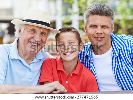 Happy senior man, his son and grandson looking at camera  - stock photo