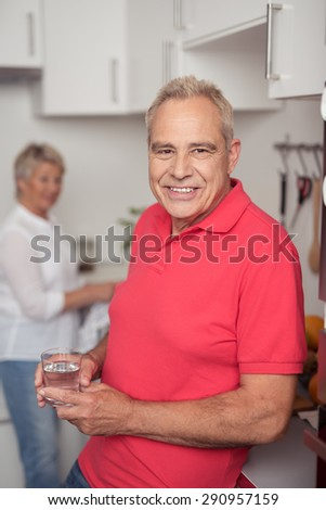 Happy Senior Man Holding a Glass of Water While Leaning his Back Against the Table at the Kitchen and Looking at the Camera. - stock photo
