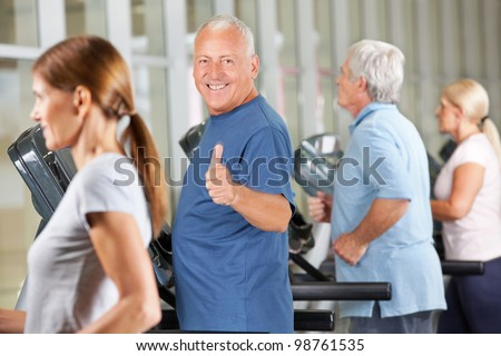 Happy senior man holding thumbs up on treadmill in gym - stock photo