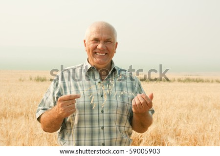 Happy senior man in field with ears of barley and wheat - stock photo
