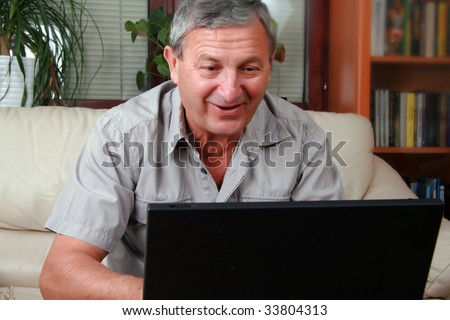 Happy senior man in front of a PC - stock photo