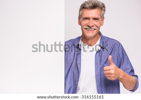 Happy senior man is holding blank placard on white background and showing thumb up. - stock photo