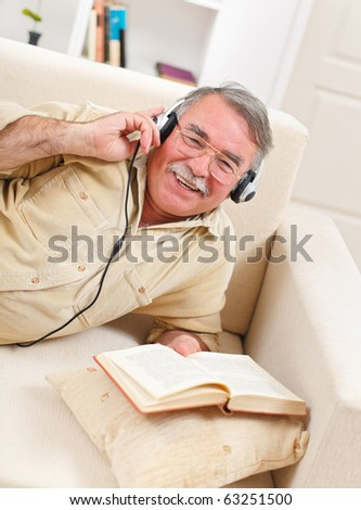 Happy senior man laying on sofa, reading and listening to music