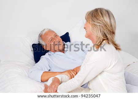Happy senior man lying in bed with mature woman sitting beside him - stock photo