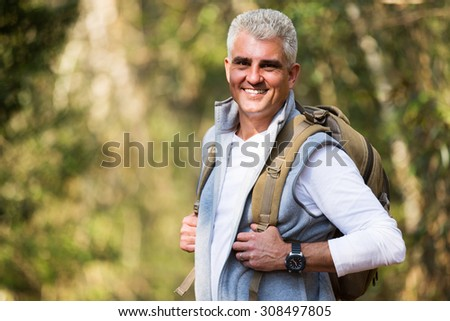 happy senior man on hike looking at the camera