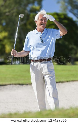 Happy senior man playing golf in a sand trap or bunker on a golf course looking at his successful shot - stock photo